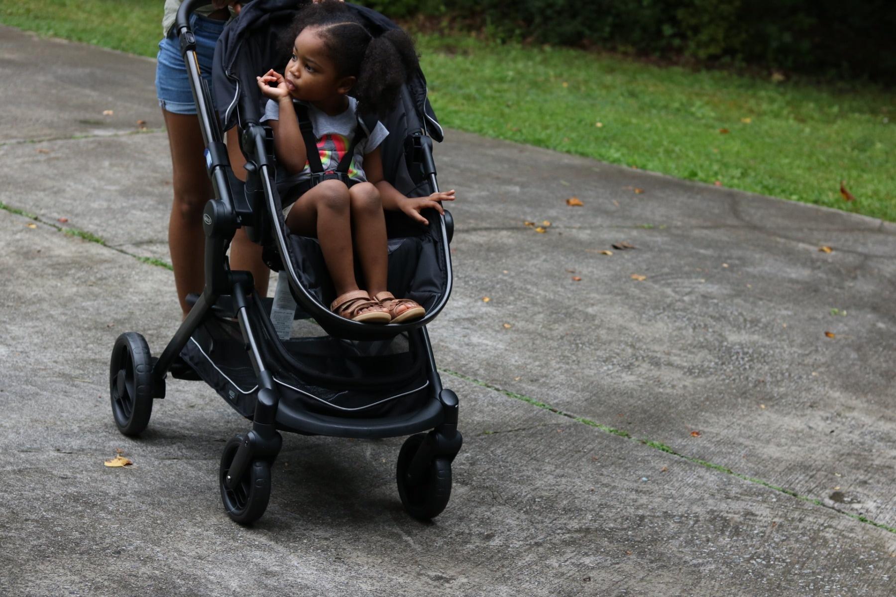 girl in pram in park bobux driftwood sandal